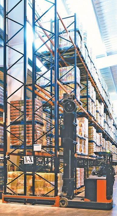 Imagen de una grúa horquilla retráctil de doble fondo utilizada en una bodega de productos alimentarios de gran consumo.